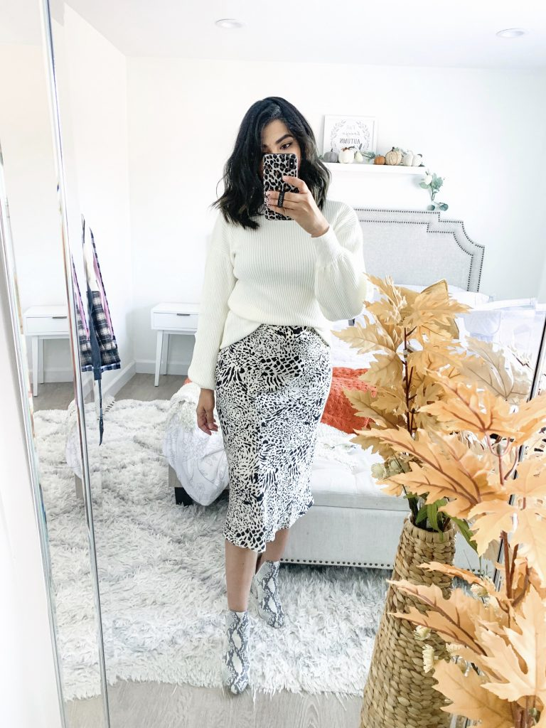 white sweater with white snake skin printed satin skirt and white snake skin printed booties