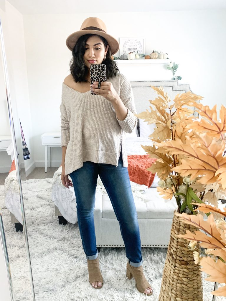 brown fedora hat with oversized tan sweater blue jeans and brown booties